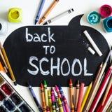 De nouveau à l'étiquette de tableau d'école avec des fournitures scolaires sur le fond de tableau noir Préparez pour votre concep photos stock