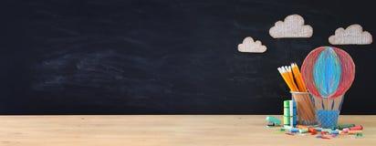 De nouveau à la bannière de concept d'école ballon d'air chaud et crayons devant le tableau noir de salle de classe images libres de droits