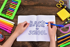 De nouveau au concept d'école avec l'écriture des textes par l'écolière dans le notebo Photographie stock libre de droits