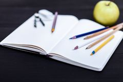 De nouveau au concept d'école, crayons colorés sur la table noire, accessoires multicolores de papeterie pour l'enfant d'enseigne image libre de droits
