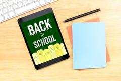 De nouveau au mot d'école sur l'écran de comprimé avec le crayon et le keyboa de livre Image stock