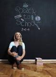 De nouveau au professeur de femme d'école souriant par le tableau noir photos libres de droits