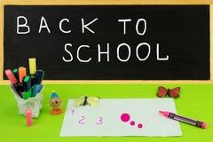De nouveau au tableau noir d'école avec des accessoires d'école et à un papier SH photos stock