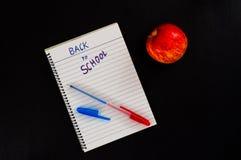 De nouveau au texte d'école en bloc-notes rayé avec le stylo et à la pomme rouge sur le fond en bois noir Image libre de droits