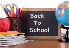 De nouveau au texte d'école sur un tableau noir avec des fournitures scolaires Photo stock