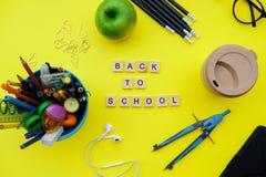 De nouveau aux blocs en bois d'école avec des fournitures scolaires et l'APPL vert Photos libres de droits