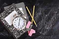 De nouveau aux fournitures scolaires et au réveil Photographie stock libre de droits