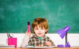 De nouveau ? l'?cole preschooler L'enfant apprend dans la classe sur le fond du tableau noir Élève du cours préparatoire près du  image stock