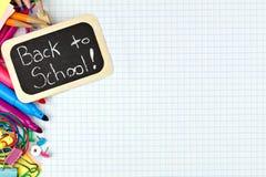 De nouveau à l'étiquette d'école avec des fournitures scolaires sur le papier de graphique Photos libres de droits