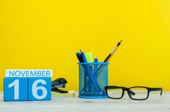 16 de novembro Dia 16 do mês, calendário de madeira da cor no fundo amarelo com materiais de escritório Autumn Time Imagens de Stock