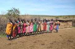 15 de noviembre de 2015, Masai Mara, Kenia, África Mujeres colorido vestidas del Masai que consiguen listas para cantar Imagen de archivo libre de regalías