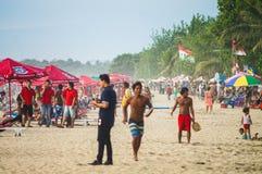 24 de noviembre de 2012 Playa del kuta de Bali Los turistas caminan a lo largo de la muchedumbre fotos de archivo
