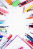 De nuevo al libro del bosquejo del espacio en blanco de la escuela y a las herramientas coloridas de la escuela en el fondo blanc Fotos de archivo libres de regalías