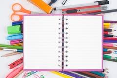 De nuevo al libro del bosquejo del espacio en blanco de la escuela y a las herramientas coloridas de la escuela en el fondo blanc Imagenes de archivo