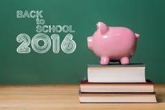 De nuevo al texto de la escuela 2016 con la hucha rosada encima de los libros Imagen de archivo libre de regalías