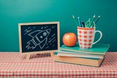De nuevo a concepto de la escuela con la pizarra, los libros y la manzana Imagen de archivo libre de regalías