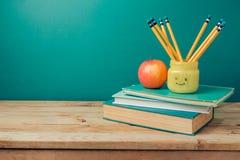 De nuevo a concepto de la escuela con los libros, los lápices en tarro del emoji y la manzana Fotos de archivo