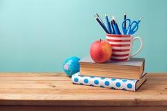 De nuevo a concepto de la escuela con los libros, los lápices en taza, la manzana, y el globo Imagenes de archivo