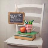 De nuevo a concepto de la escuela con los libros, los lápices en taza y la pizarra Imágenes de archivo libres de regalías