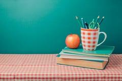 De nuevo a concepto de la escuela con los libros, los lápices y la manzana en mantel Imagenes de archivo