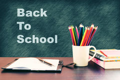 De nuevo a concepto de la escuela con los libros y el lápiz del color en etiqueta de madera Imagen de archivo libre de regalías