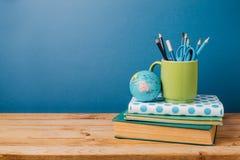 De nuevo a concepto de la escuela con los libros y el lápiz en taza en la tabla de madera Imagen de archivo libre de regalías