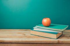 De nuevo a concepto de la escuela con los libros y la manzana en la tabla de madera Foto de archivo