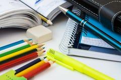 De nuevo a concepto de la escuela, fuentes, lápices multicolores, libretas, highlighter, pluma, libro de texto, caucho, mesa blan Foto de archivo