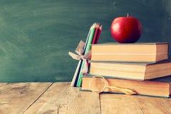 De nuevo a concepto de la escuela Pizarra con los libros y la manzana Imagen de archivo libre de regalías