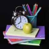De nuevo a concepto de la escuela. Una manzana, lápices coloreados y un despertador en la pila de libros sobre negro Fotografía de archivo libre de regalías