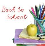 De nuevo a concepto de la escuela. Una manzana, lápices coloreados y vidrios en la pila de libros aislados en el fondo blanco. Imágenes de archivo libres de regalías