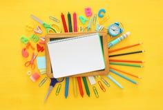 De nuevo a concepto de la escuela Visión superior Cuaderno de la escuela en la madera amarilla Foto de archivo
