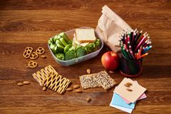 De nuevo a concepto de la escuela, a fuentes de escuela, a las galletas y a la caja del almuerzo en el escritorio de madera, foco Imagen de archivo libre de regalías