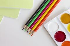 De nuevo a concepto de la escuela Lápices, cuadernos y pintura multicolores en el fondo blanco fotografía de archivo