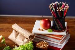 De nuevo a concepto de la escuela, las fuentes de escuela, galletas, embalaron el almuerzo y la caja del almuerzo en el escritori Fotos de archivo libres de regalías