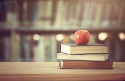 De nuevo a concepto de la escuela pila de libros sobre el escritorio de madera delante de la biblioteca y de estantes con los lib Imagenes de archivo