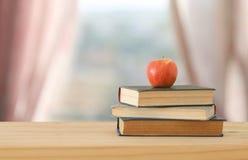 De nuevo a concepto de la escuela pila de libros sobre el escritorio de madera delante de la ventana de la luz del día Imagen de archivo