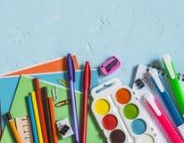 De nuevo a escuela Accesorios de la escuela - cuadernos, plumas, lápices, pintura en un fondo azul, visión superior Concepto de l imagenes de archivo