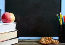 De nuevo a escuela, concepto de la educación Libros, galletas integrales útiles y manzana en la tabla de la sala de clase delante fotos de archivo
