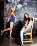 De nuevo a escuela después de vacaciones de verano, dos muchachas adolescentes en sala de clase con la pizarra pintada Imágenes de archivo libres de regalías