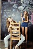 De nuevo a escuela después de vacaciones de verano, dos muchachas adolescentes en sala de clase con la pizarra pintada junto Fotografía de archivo