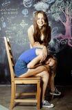 De nuevo a escuela después de vacaciones de verano, dos muchachas adolescentes en sala de clase con la pizarra pintada junto Foto de archivo libre de regalías