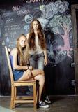 De nuevo a escuela después de vacaciones de verano, dos muchachas adolescentes en sala de clase con la pizarra pintada junto Fotografía de archivo libre de regalías