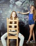 De nuevo a escuela después de vacaciones de verano, dos muchachas adolescentes en sala de clase con la pizarra pintada junto Imagenes de archivo
