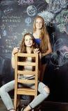 De nuevo a escuela después de vacaciones de verano, dos muchachas adolescentes en sala de clase con la pizarra pintada junto Imagen de archivo