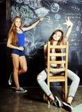 De nuevo a escuela después de vacaciones de verano, dos muchachas adolescentes en sala de clase con la pizarra pintada junto Fotos de archivo
