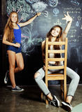 De nuevo a escuela después de vacaciones de verano, dos muchachas adolescentes en sala de clase con la pizarra pintada junto Foto de archivo