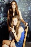 De nuevo a escuela después de vacaciones de verano, dos muchachas adolescentes en sala de clase con la pizarra pintada junto Imagen de archivo libre de regalías