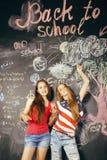 De nuevo a escuela después de vacaciones de verano, dos muchachas reales adolescentes en sala de clase con la pizarra pintada jun Foto de archivo libre de regalías