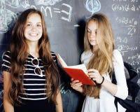 De nuevo a escuela después de vacaciones de verano, dos muchachas reales adolescentes en sala de clase con la pizarra pintada jun Fotos de archivo libres de regalías